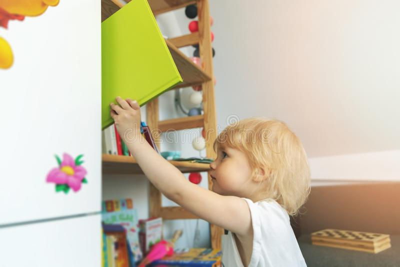 A criança toma o livro da estante fotografia de stock royalty free