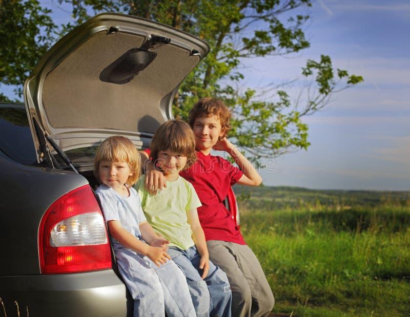 Criança três alegre que senta-se no tronco de um carro fotos de stock