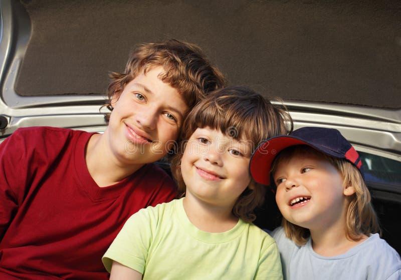 Criança três alegre que senta-se no tronco de um carro imagem de stock royalty free