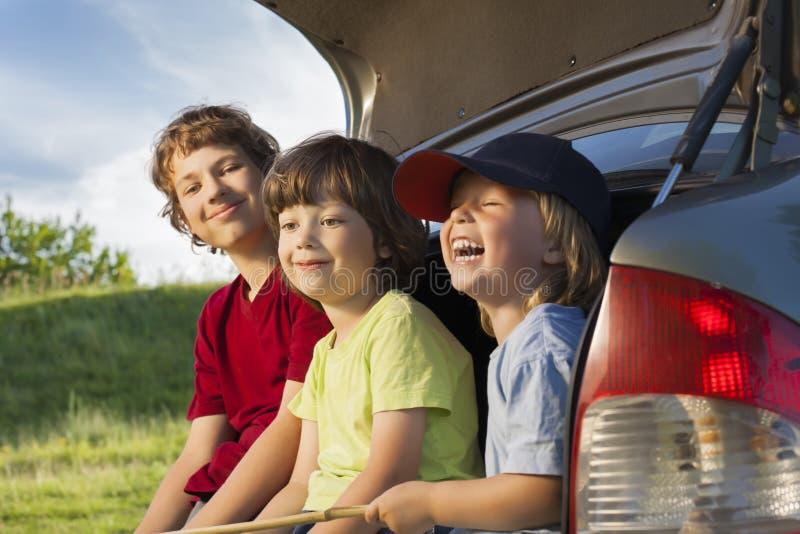 Criança três alegre que senta-se no tronco de um carro imagens de stock