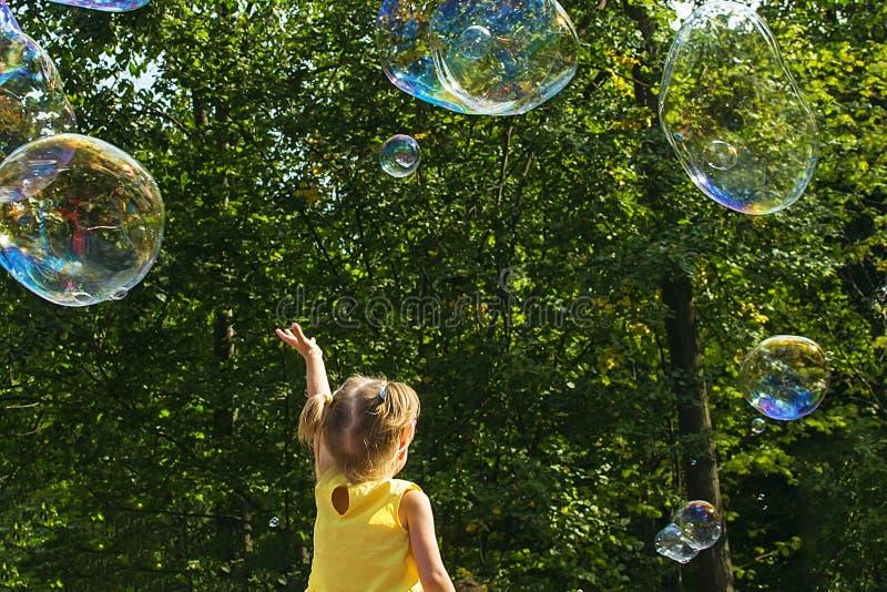 A criança trava bolhas de sabão imagens de stock