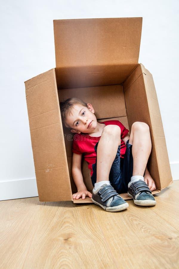 Criança triste cansada que senta-se no cartão, procurando para a confiança imagem de stock royalty free