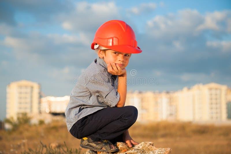 Criança triste cansado pequena bonito no capacete alaranjado que senta-se no fundo de construções novas e do céu nebuloso do por  imagens de stock