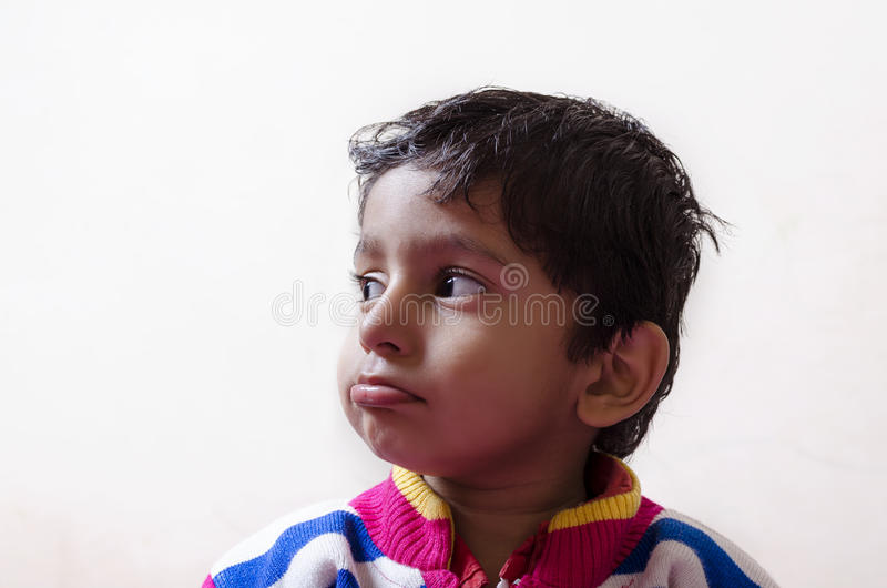 Criança triste do menino que olha o close up lateral fotografia de stock