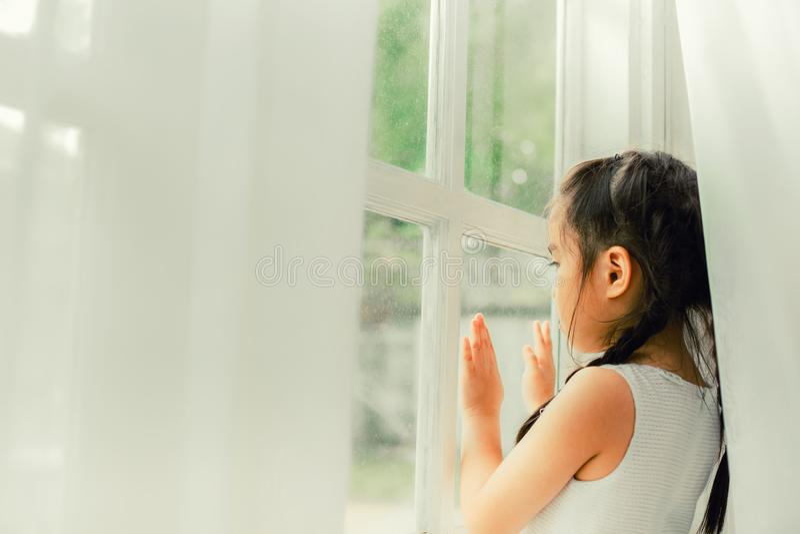 Criança triste, menina que olha a chuva imagens de stock royalty free