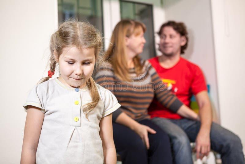 Criança triste no fundo de pais felizes, paizinho novo na família imagem de stock royalty free