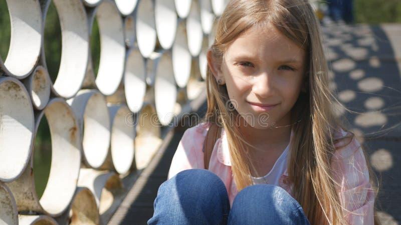 Criança triste no parque, menina pensativa infeliz exterior, criança pensativa furada na ponte fotos de stock royalty free