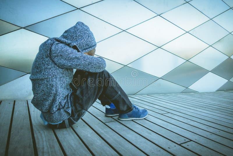 Criança triste, só, infeliz, desapontado que senta-se apenas na terra fora imagem de stock royalty free