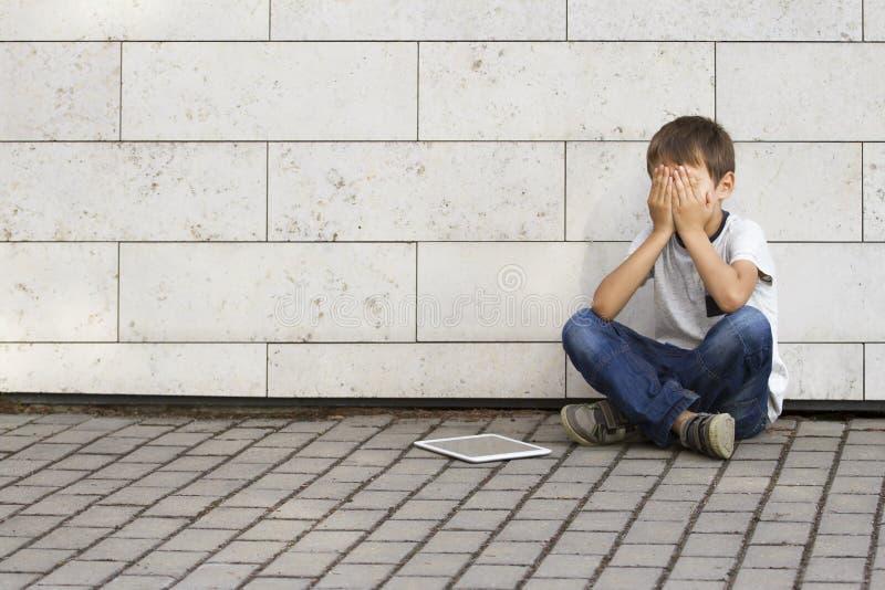 Criança triste, só, infeliz, desapontado que senta-se apenas na terra O menino que guarda sua cabeça, olha para baixo O PC da tab fotografia de stock royalty free