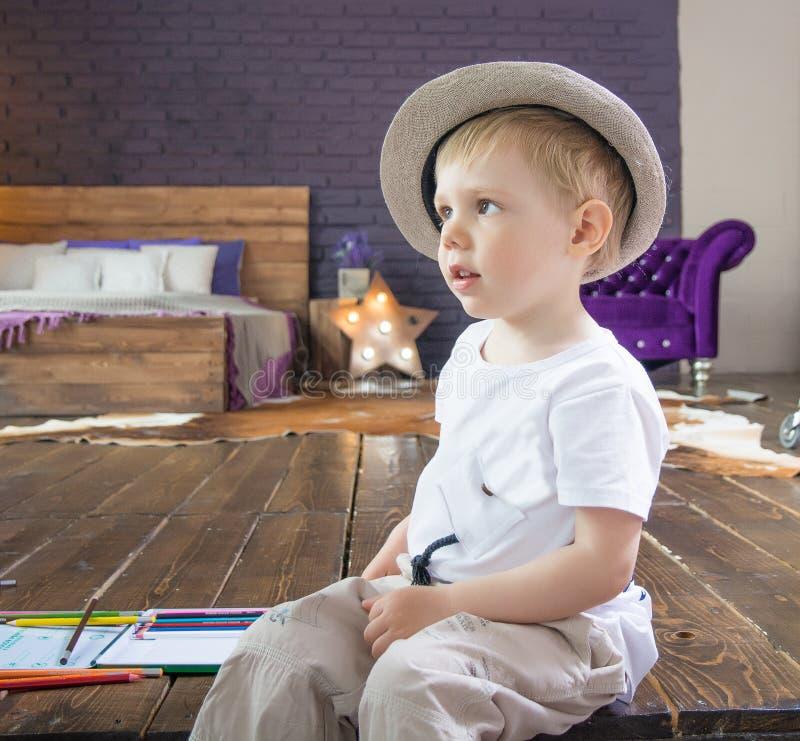 A criança, um rapaz pequeno que senta-se nas escadas no estúdio, em um chapéu elegante fotos de stock royalty free