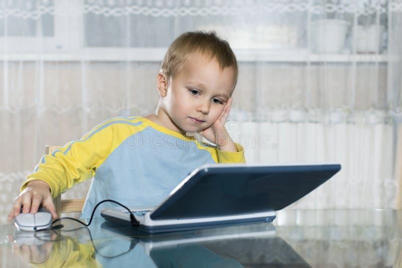 A criança usa um computador do jogo do ` s das crianças imagens de stock royalty free