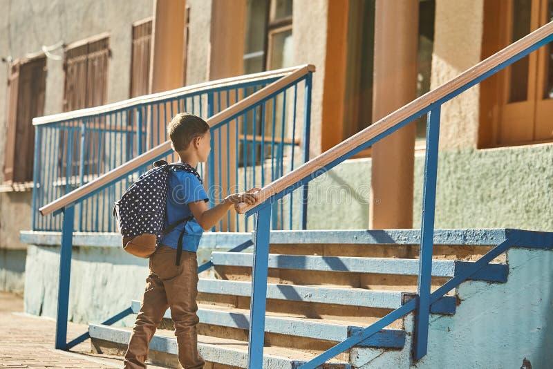 A criança vai à escola menino estudante vai para a escola de manhã criança feliz com uma pasta nas costas e livros didáticos em imagem de stock