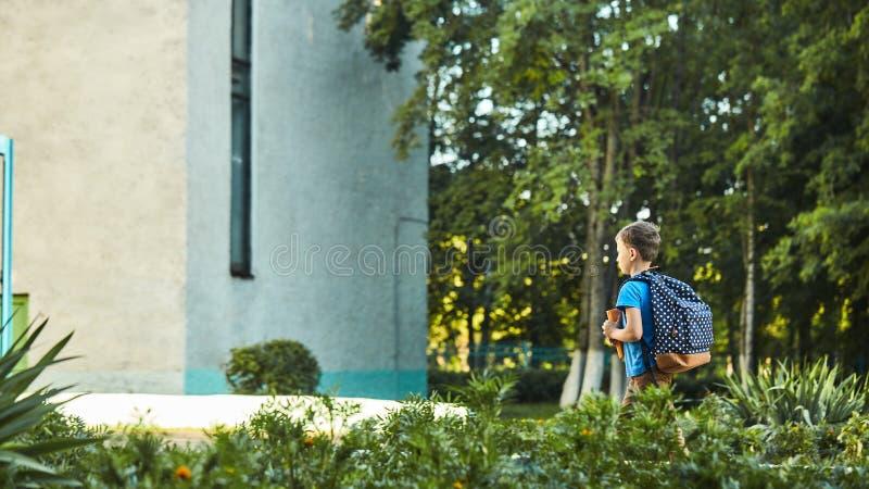 A criança vai à escola menino estudante vai para a escola de manhã criança feliz com uma pasta nas costas e livros didáticos em fotos de stock royalty free