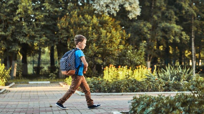 A criança vai à escola menino estudante vai para a escola de manhã criança feliz com uma pasta nas costas e livros didáticos em foto de stock royalty free
