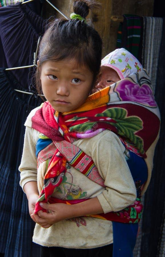 A criança vietnamiana leva o irmão mais novo nela para trás fotos de stock