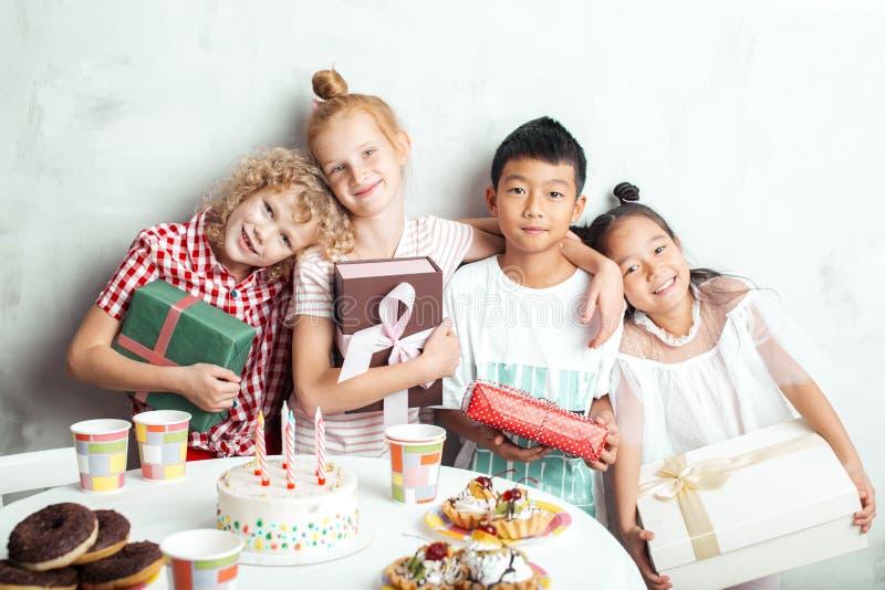 Crianças étnicas com os presentes que levantam à câmera imagem de stock royalty free