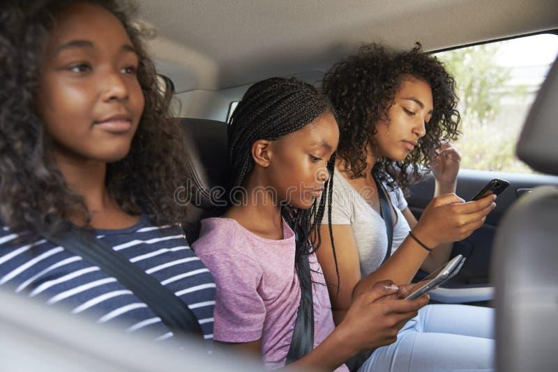 Crianças adolescentes que usam dispositivos de Digitas na viagem por estrada da família imagem de stock royalty free
