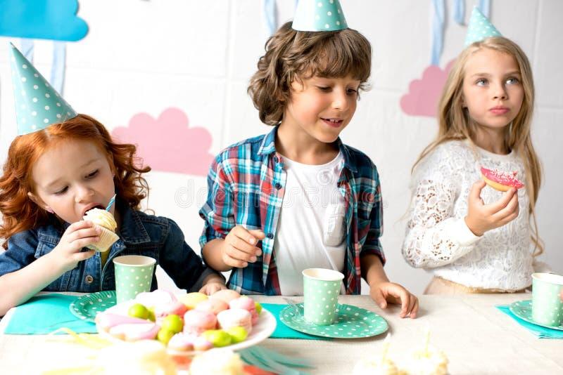 crianças adoráveis em chapéus do partido que comem doces deliciosos fotos de stock royalty free