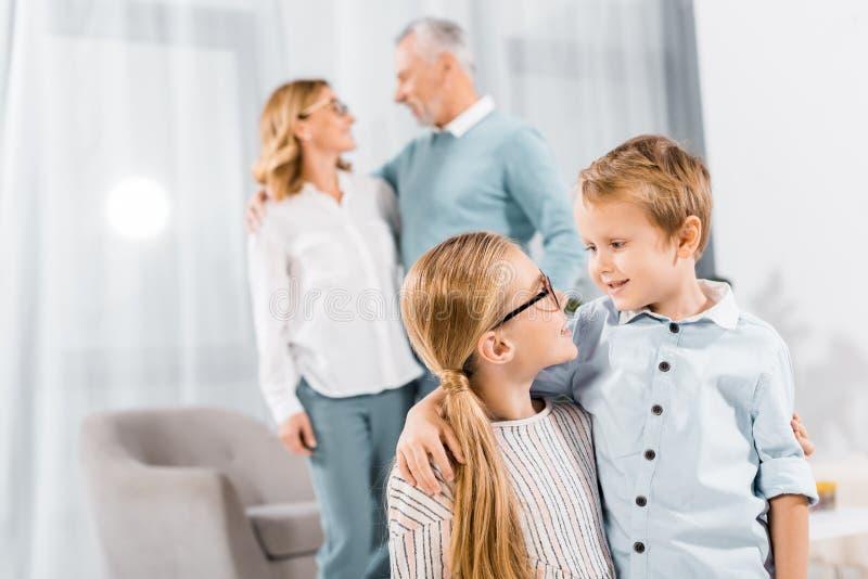 crianças adoráveis olhando umas para as outras e abraçando enquanto seus avós estão atrás foto de stock