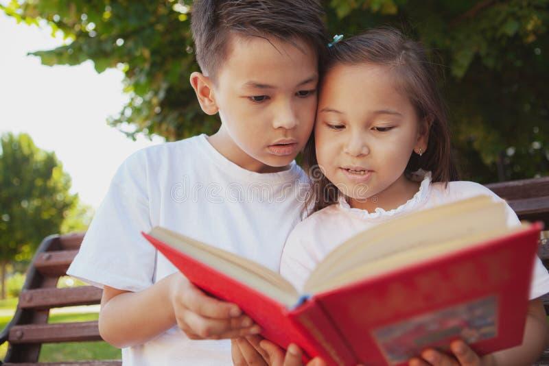 Crianças adoráveis que apreciam o dia ensolarado morno no parque imagens de stock royalty free