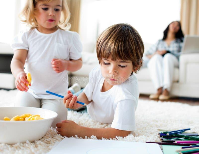 Crianças adoráveis que comem microplaquetas e desenhar imagem de stock royalty free