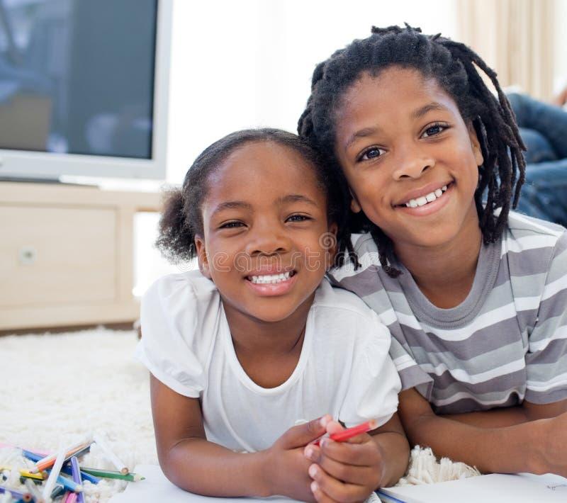 Crianças adoráveis que desenham o encontro para baixo no assoalho imagem de stock royalty free