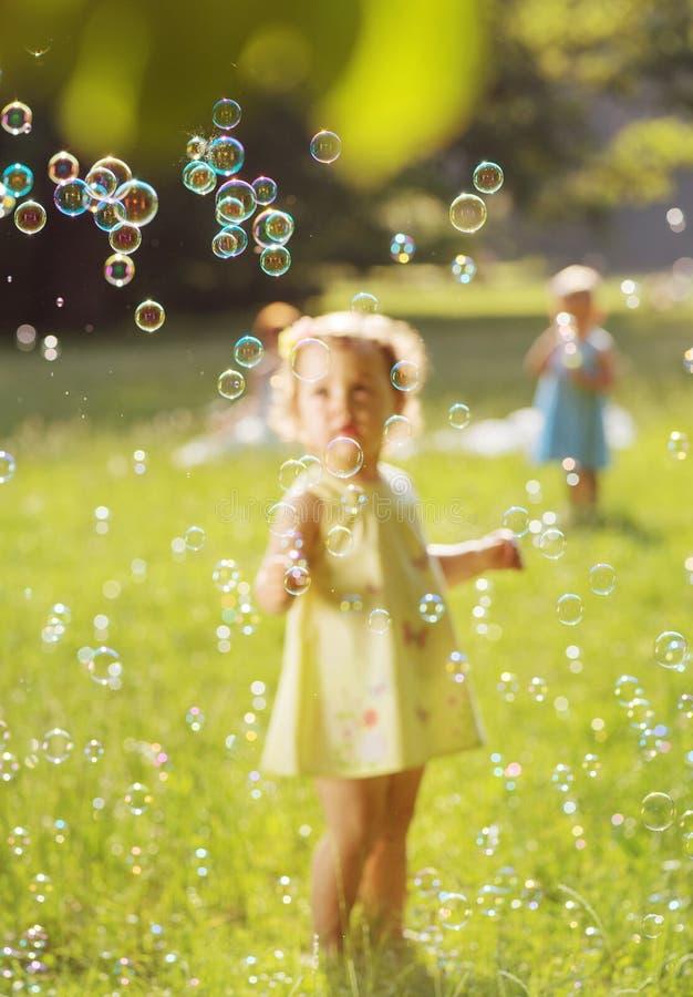 Crianças adoráveis que fundem as bolhas de sabão fotos de stock