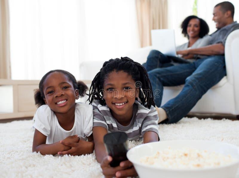Crianças adoráveis que prestam atenção à televisão foto de stock royalty free