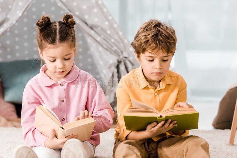 crianças adoráveis sentadas em tapete e imagem de stock royalty free