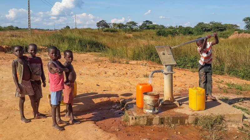 Crianças africanas locais que bombeiam a água potável no construído bem por c fotografia de stock