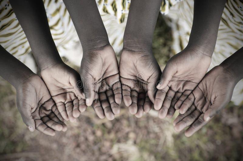 Crianças africanas que mantêm as mãos colocadas para implorar a ajuda Africano pobre foto de stock