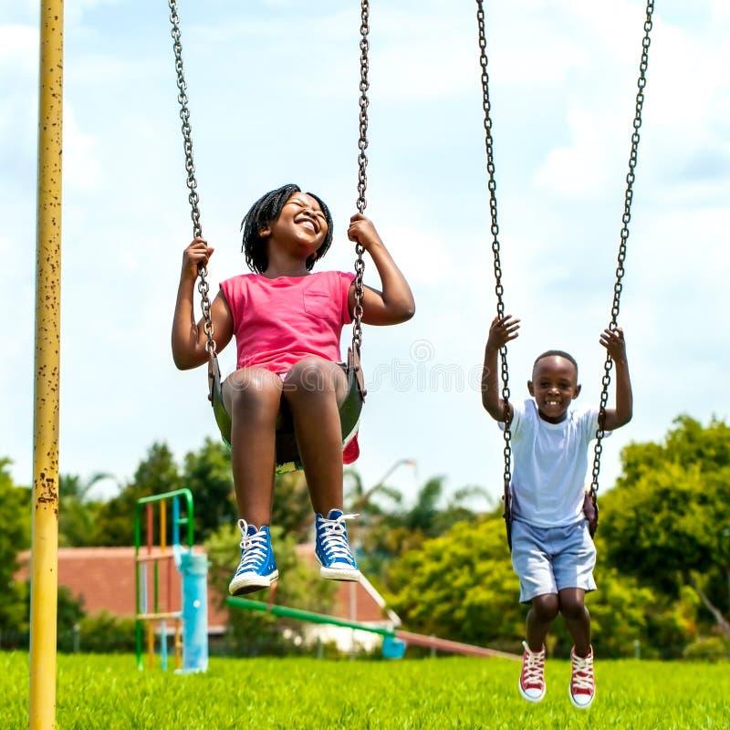 Crianças africanas que têm o divertimento que balança no parque imagem de stock royalty free