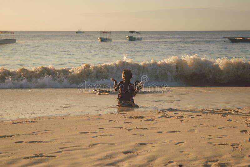 Crianças afro-americanos pobres que jogam com a garrafa no oceano foto de stock