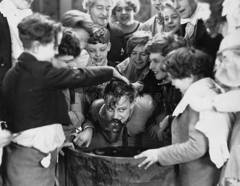 Crianças aglomeradas em torno de sacudir-se da maçã (todas as pessoas descritas não são umas vivas mais longo e nenhuma proprieda fotos de stock royalty free