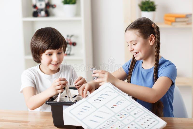 Crianças agradáveis que sentam-se na tabela fotografia de stock royalty free