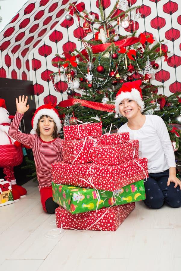 Crianças alegres com muitos presentes do Natal imagens de stock