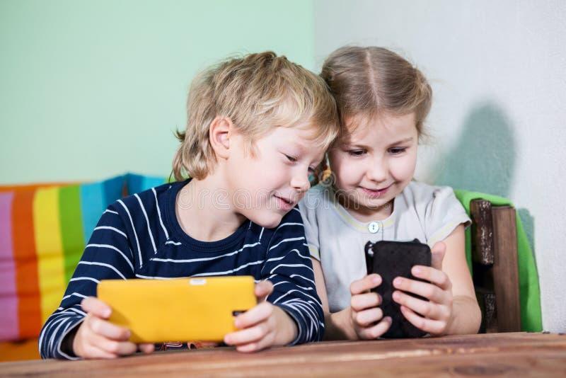 Crianças alegres com os smartphones no jogo das mãos fotografia de stock