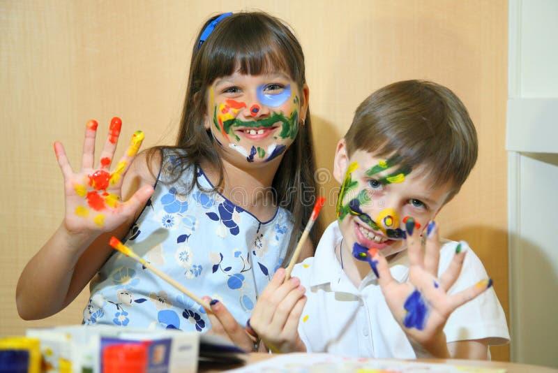 Crianças alegres com pinturas em suas caras Caras das pinturas das crianças com cores imagem de stock royalty free