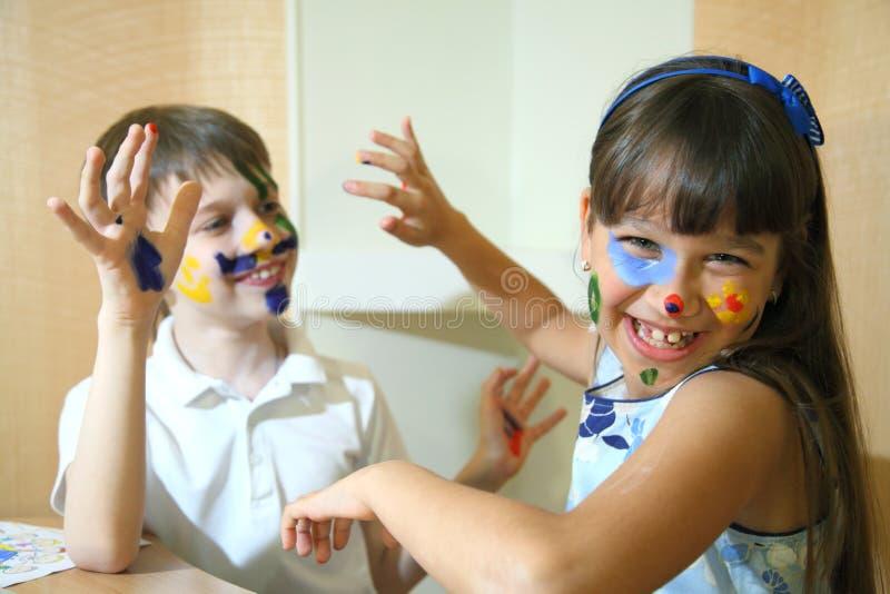Crianças alegres com pinturas em suas caras Caras das pinturas das crianças com cores fotografia de stock royalty free
