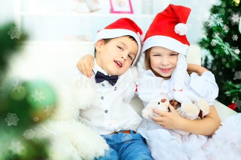 Crianças alegres em chapéus do Natal imagens de stock