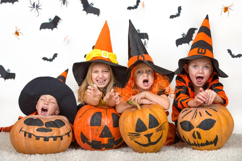 Crianças alegres em trajes do Dia das Bruxas que comemoram o Dia das Bruxas foto de stock