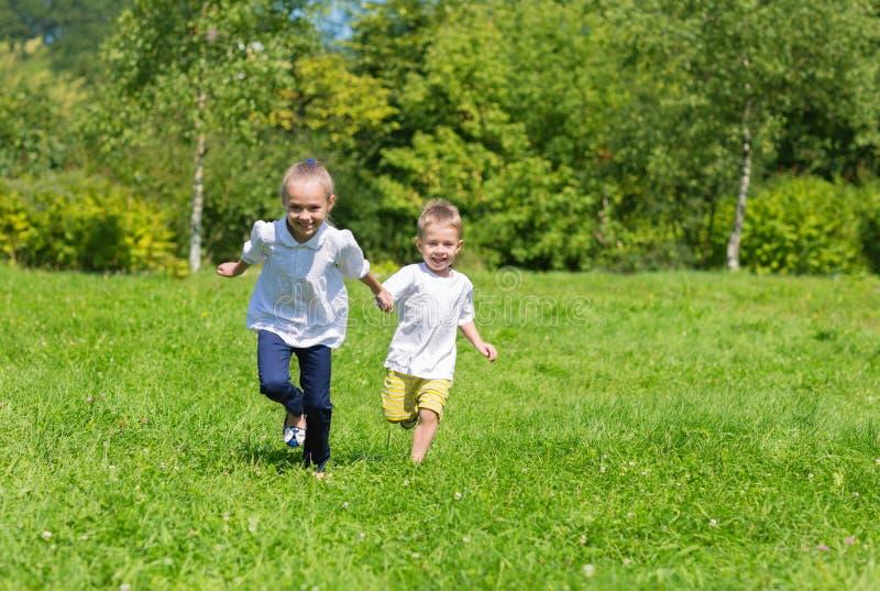 Crianças alegres felizes que correm na grama imagens de stock