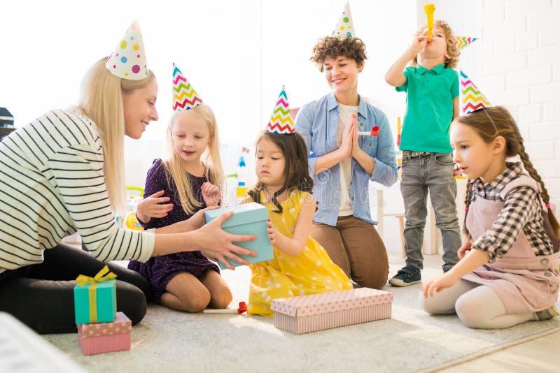 Crianças alegres que abrem a caixa de presente na festa de anos imagem de stock