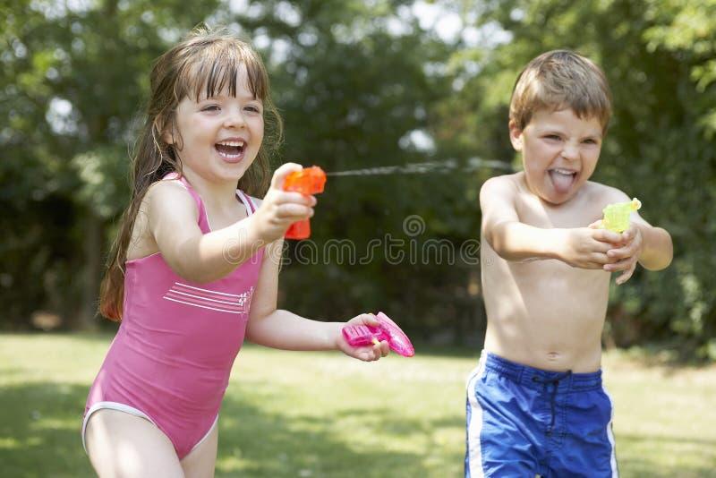 Crianças alegres que disparam em pistolas de água fotografia de stock