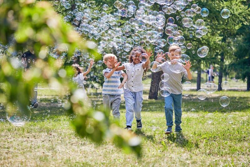 Crianças alegres que jogam com bolhas de sabão imagem de stock