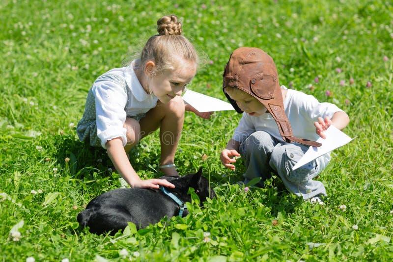 Crianças alegres que jogam com o cão, buldogue francês imagens de stock