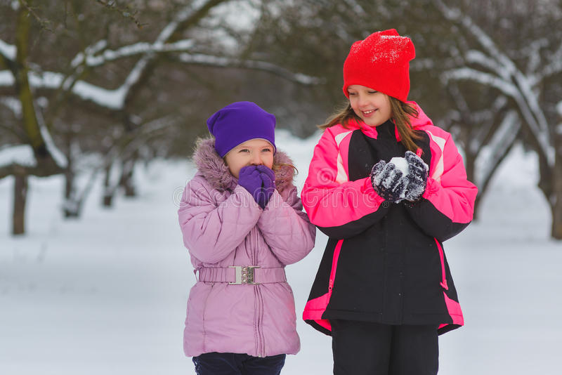 Crianças alegres que jogam na neve Duas meninas felizes que têm o divertimento fora do dia de inverno foto de stock
