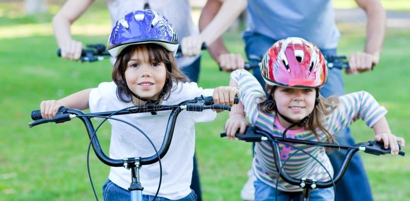 Crianças alegres que montam uma bicicleta fotografia de stock