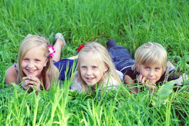 Crianças amigáveis que encontram-se na grama verde no parque do verão imagens de stock royalty free