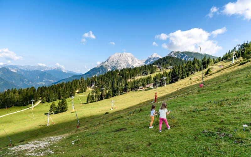 Crianças - as meninas gêmeas estão caminhando nas montanhas imagens de stock royalty free